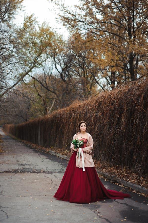 Portrait d'une belle jeune mariée dans une robe rouge avec un bouquet l'épousant dans une main photo stock