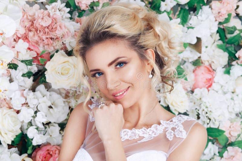 Portrait d'une belle jeune mariée de mode, doux et sensuel sur le fond de fleurs Épouser composent et des cheveux photo libre de droits