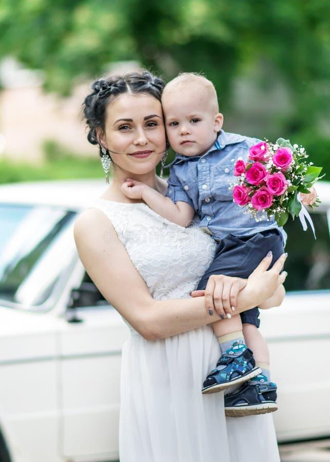 Portrait d'une belle jeune jeune mariée féminine tenant le petit bébé garçon avec le bouquet de roses de mariage et regardant dan photo libre de droits