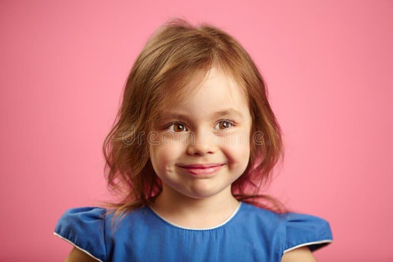Portrait d'une belle petite fille avec de jolis yeux sur un fond rose isolé photo stock