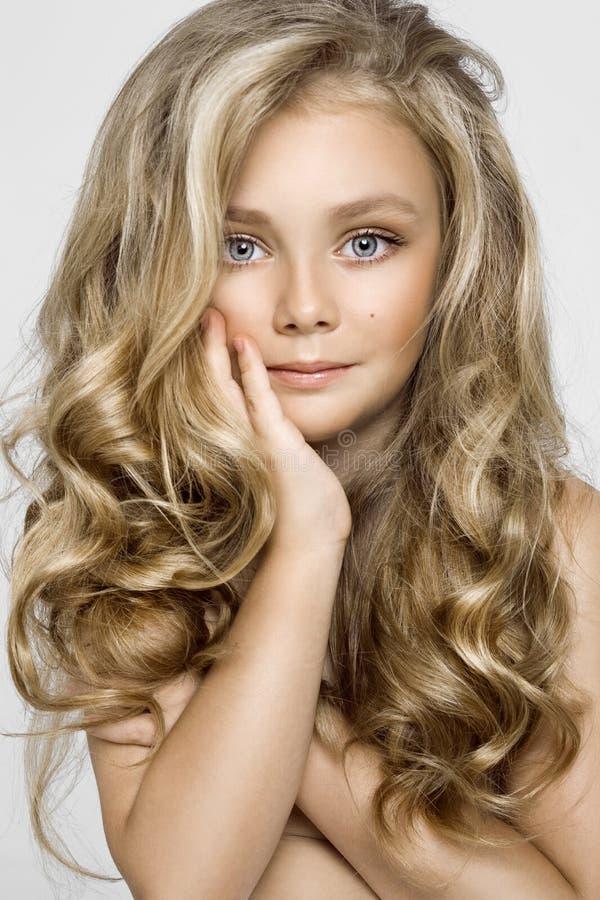 Portrait d'une belle petite fille avec de longs cheveux sur un fond blanc dans le studio images libres de droits