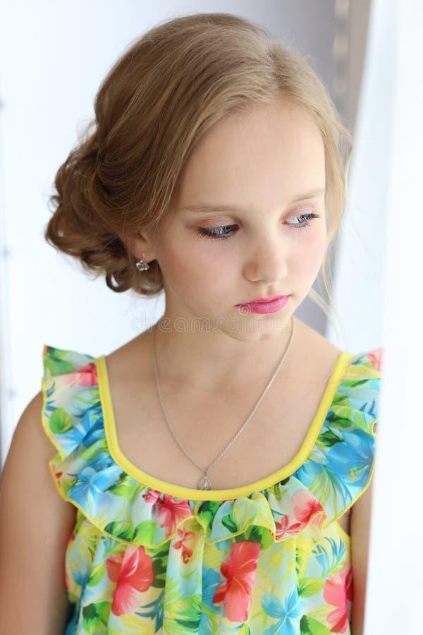 Portrait d'une belle petite fille avec des cheveux la soirée dans la robe lumineuse d'été avec le maquillage photo libre de droits
