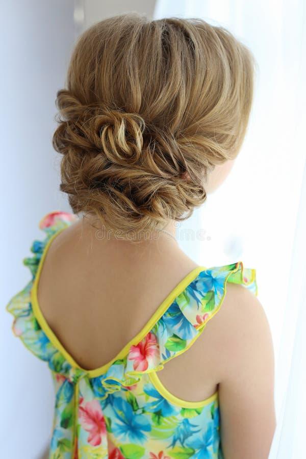 Portrait d'une belle petite fille avec des cheveux la soirée dans la robe lumineuse d'été avec le maquillage photo stock
