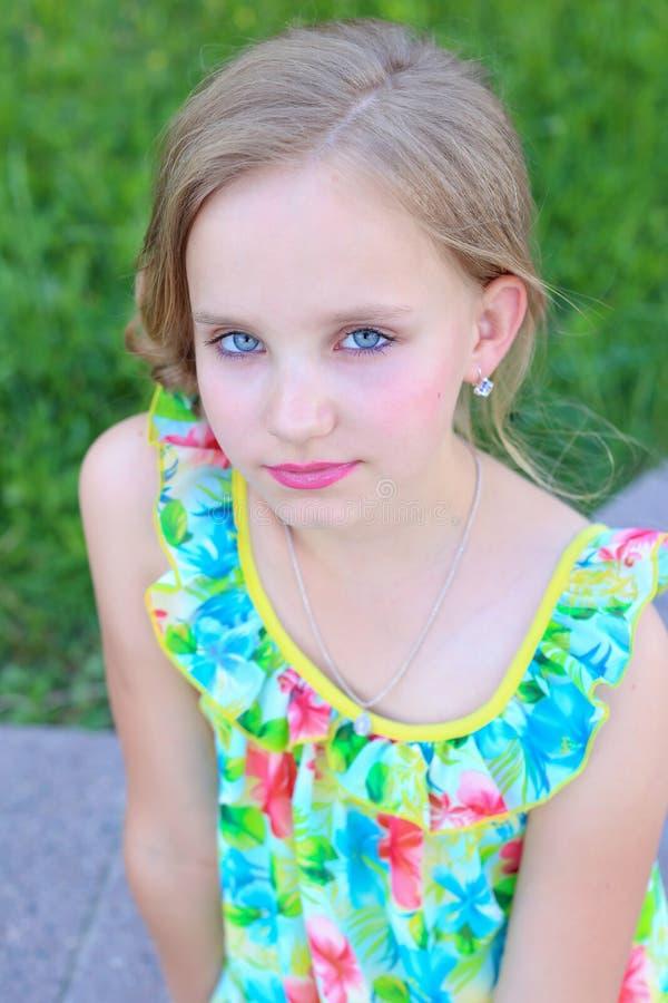 Portrait d'une belle petite fille avec des cheveux la soirée dans la robe lumineuse d'été avec le maquillage photos libres de droits