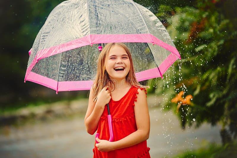 Portrait d'une belle petite fille riante sous la pluie, avec a image stock