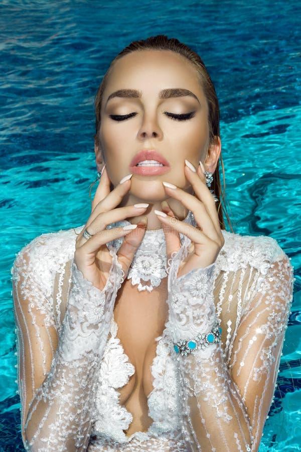Portrait d'une belle, sexy femme dans la piscine, elle a une belle manucure sur ses ongles photographie stock
