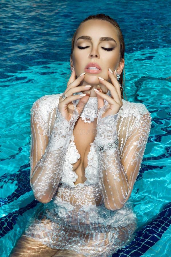Portrait d'une belle, sexy femme dans la piscine, elle a une belle manucure sur ses ongles images stock