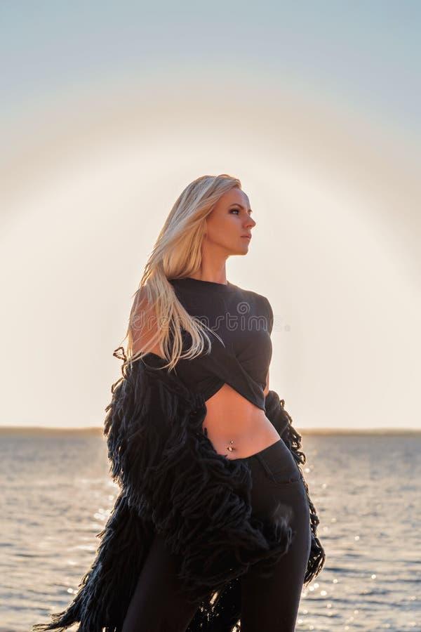 Portrait d'une blonde sexy séduisante se tenant d'un air songeur dans des vêtements noirs avec un lac de coucher du soleil sur un photos libres de droits