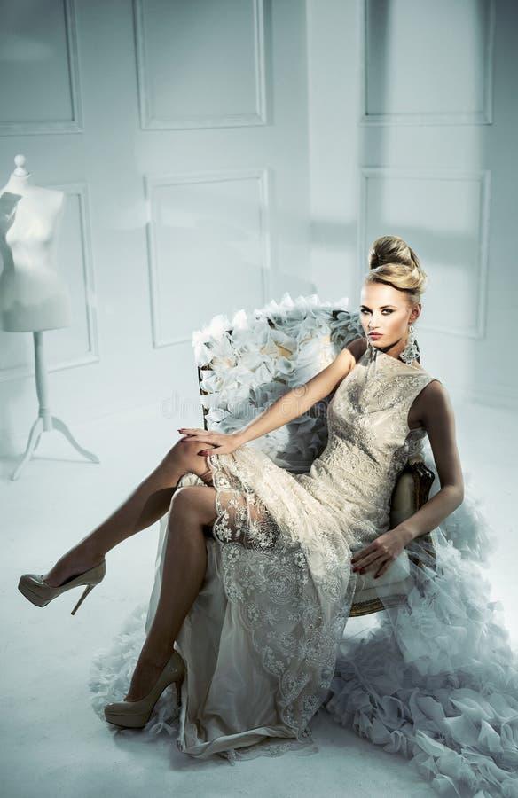 Portrait d'une dame blonde élégante s'asseyant sur le fauteuil de fantaisie images stock