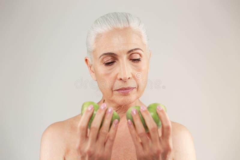 Portrait d'une demi femme agée nue attirante regardant deux tranches de pomme verte d'isolement au-dessus du fond blanc photo libre de droits
