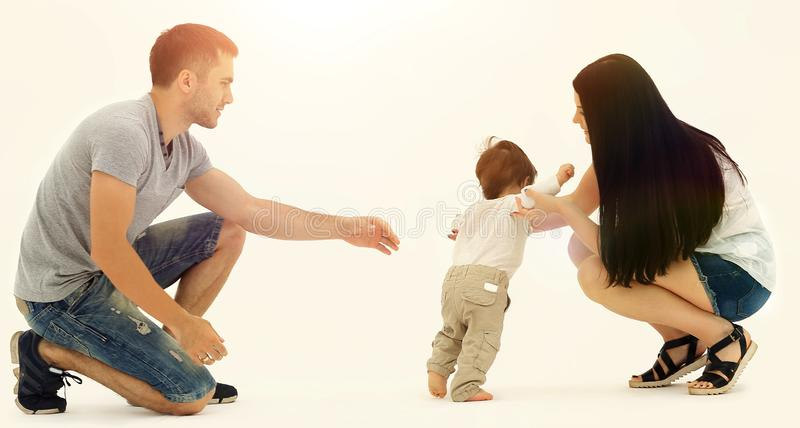 Portrait d'une famille heureuse qui enseigne un enfant à marcher photo stock