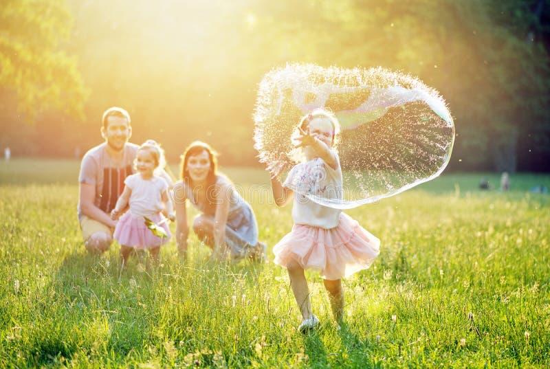 Portrait d'une famille heureuse se reposant en parc photo stock