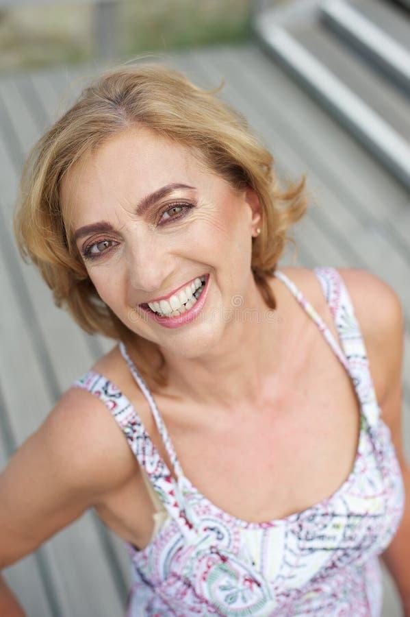 Portrait d'une femelle plus âgée attirante souriant dehors photo stock