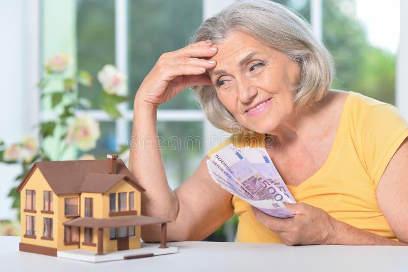 Portrait d'une femme âgée avec des billets en euros et une maison photographie stock