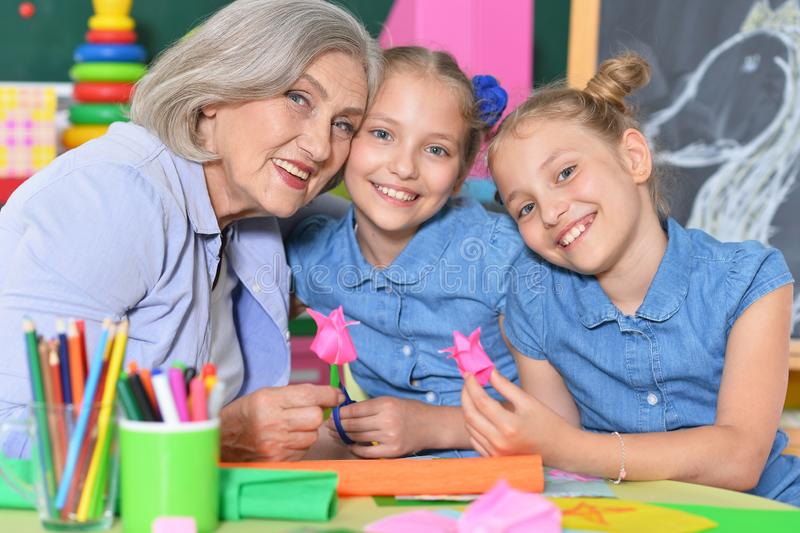 Portrait d'une femme âgée avec des filles dessinant images stock