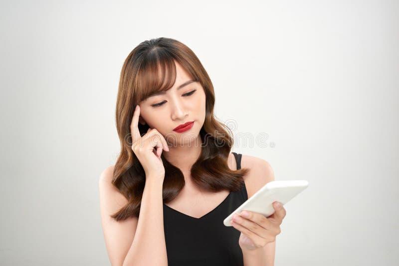 Portrait d'une femme d'affaires asiatique heureuse ? l'aide du t?l?phone portable d'isolement au-dessus du fond blanc photos stock