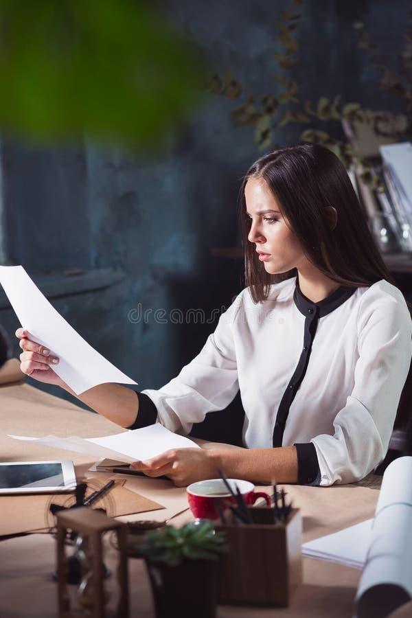 Portrait d'une femme d'affaires qui travaille au bureau photo stock
