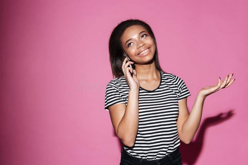 Portrait d'une femme africaine de sourire parlant au téléphone portable image libre de droits