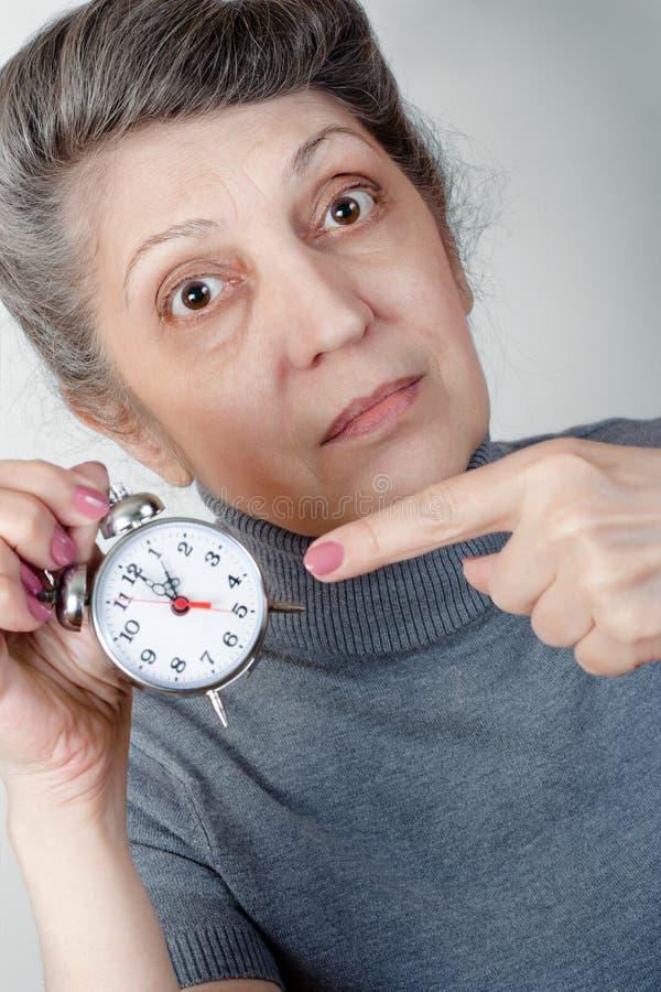 Portrait d'une femme agée avec une horloge photos libres de droits