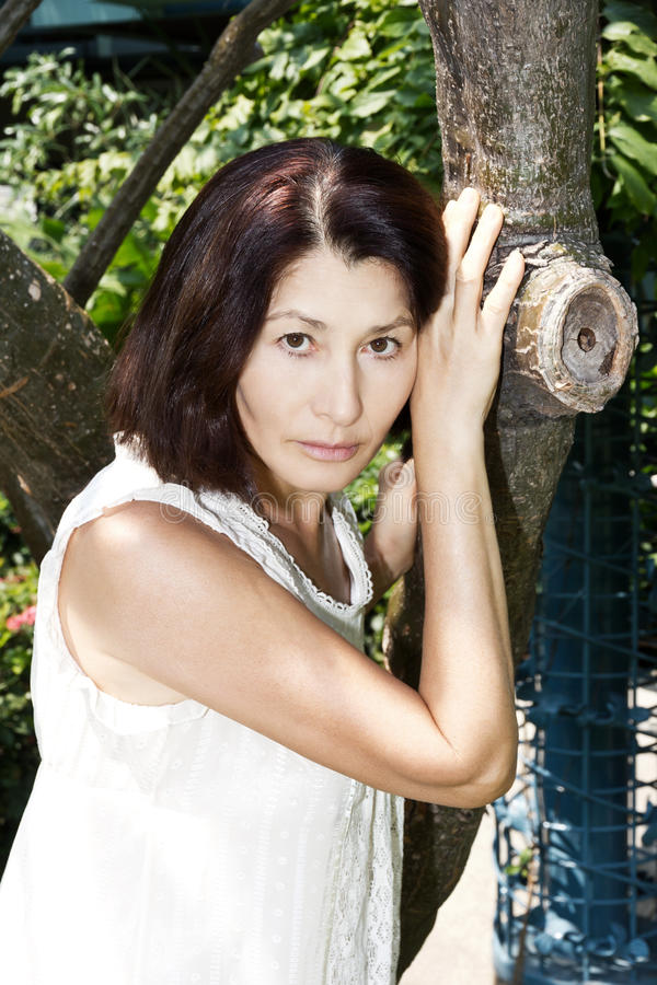 Portrait d'une femme agée près de l'arbre image libre de droits