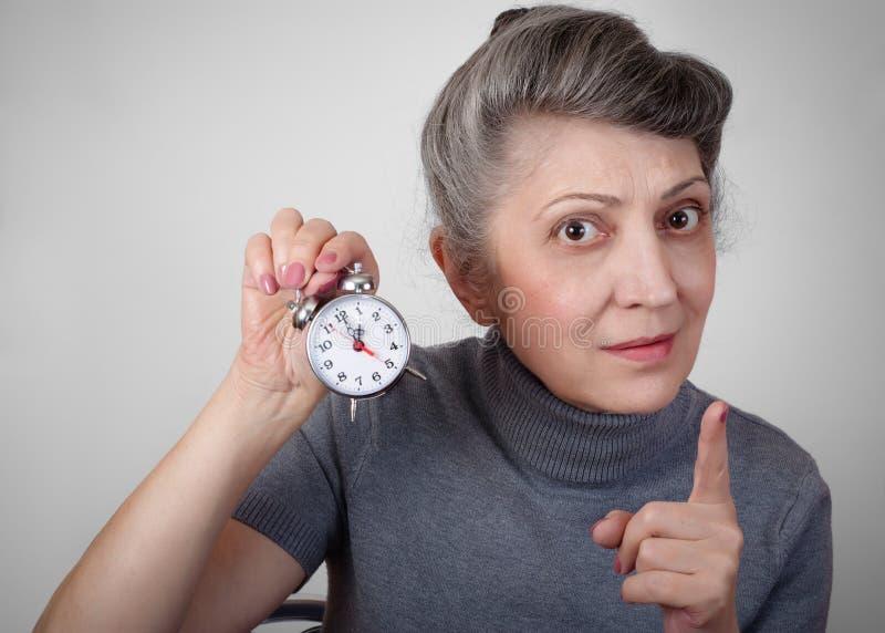 Portrait d'une femme agée tenant une horloge photographie stock libre de droits