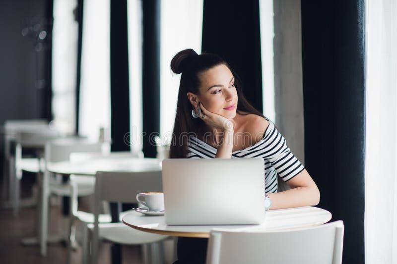 Portrait d'une femme attirante s'asseyant dans un certain café avec son ordinateur portable et pensant au-dessus d'un sujet tout  image stock