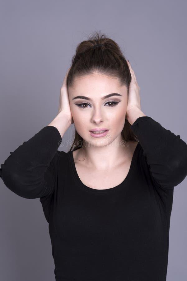Portrait d'une femme avec des mains sur des oreilles image stock