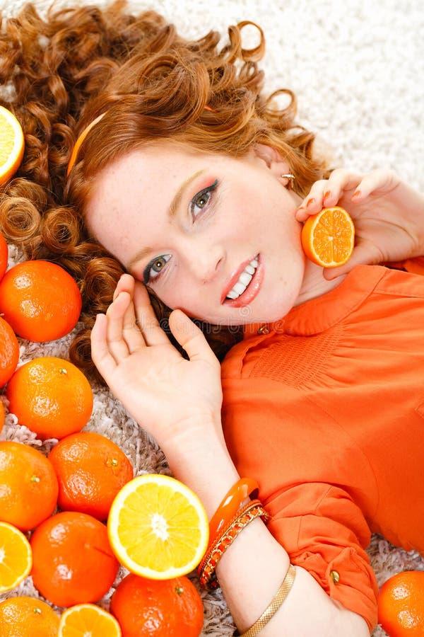 Portrait d'une femme avec des oranges sur le blanc image libre de droits