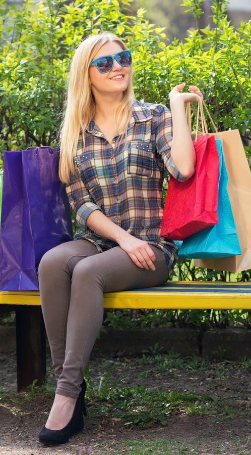 portrait d'une femme avec des paniers sur le banc photos stock