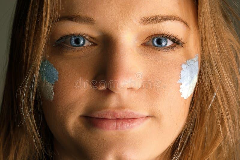 Portrait d'une femme avec le drapeau de l'Argentine peinte sur son visage photo stock
