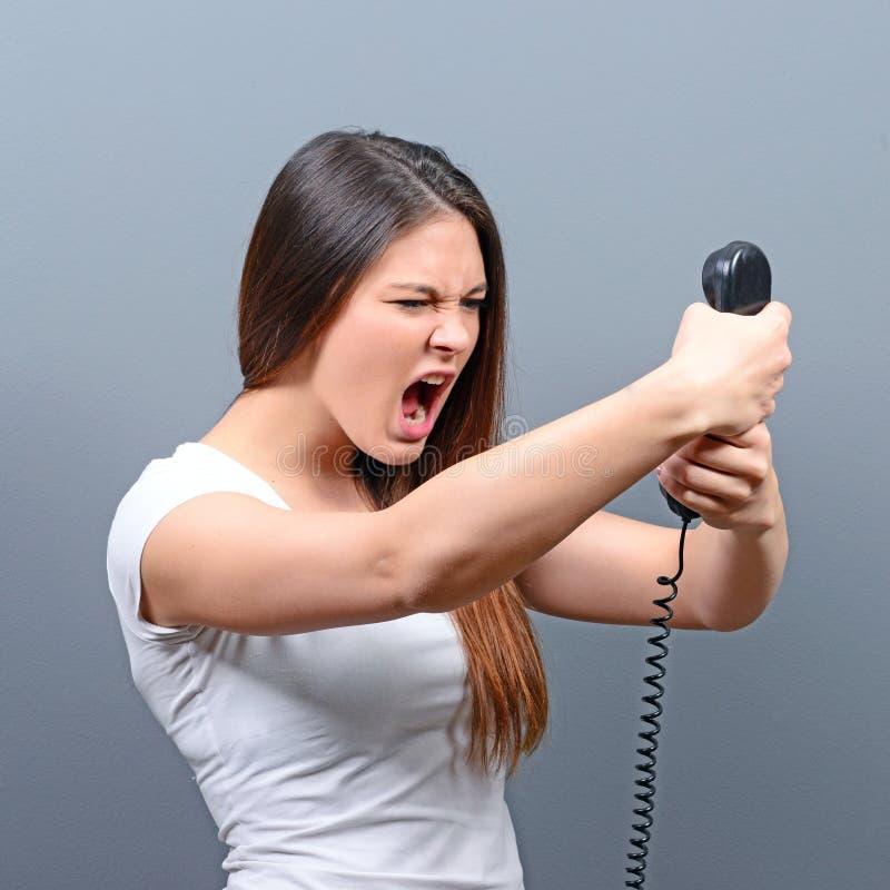 Portrait d'une femme ayant un appel téléphonique désagréable sur fond gris images stock