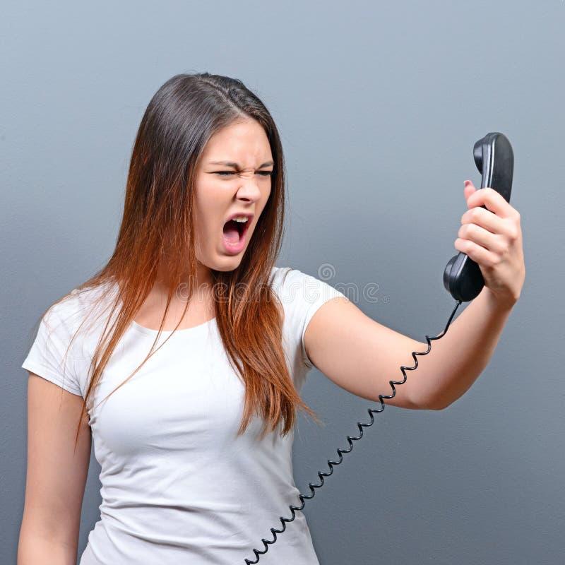Portrait d'une femme ayant un appel téléphonique désagréable sur fond gris photos libres de droits