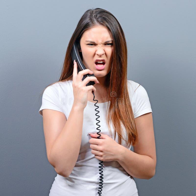 Portrait d'une femme ayant un appel téléphonique désagréable sur fond gris photographie stock libre de droits