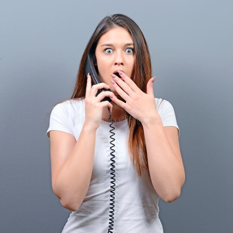 Portrait d'une femme ayant un appel téléphonique désagréable sur fond gris image libre de droits