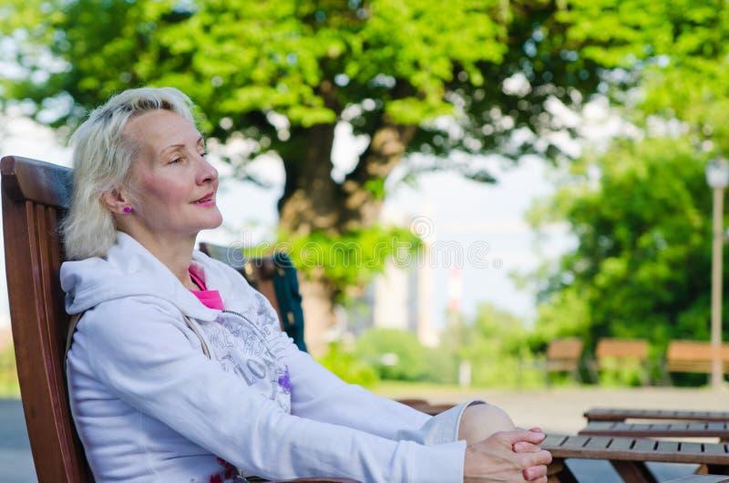 Portrait d'une femme détendant à un café d'été photographie stock libre de droits