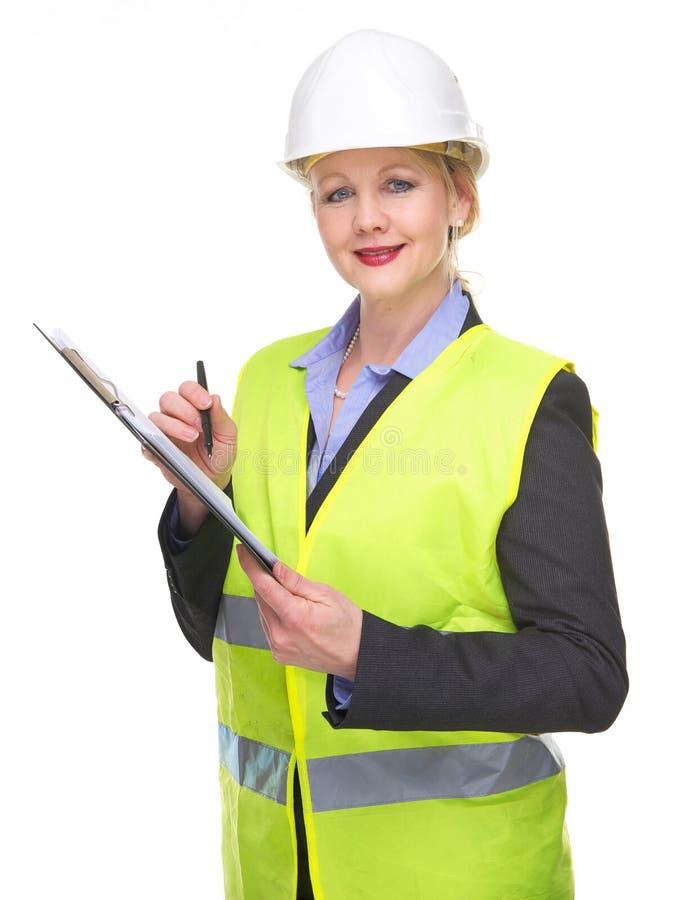 Portrait d'une femme d'affaires dans l'écriture de gilet de sécurité et de casque antichoc sur le presse-papiers photo libre de droits