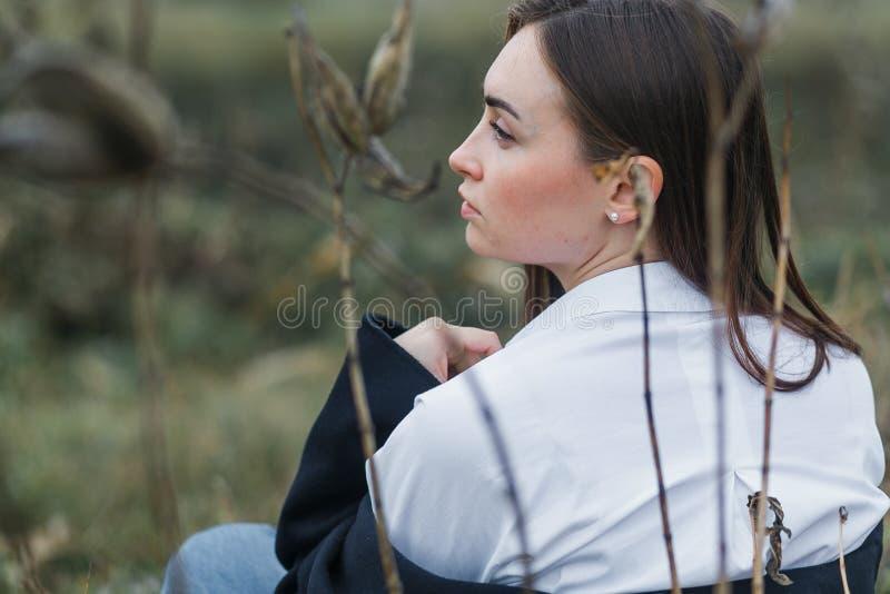 Portrait d'une femme dans la chemise blanche, se reposant avec de nouveau à l'appareil-photo, regardant du côté gauche Forêt auto image stock