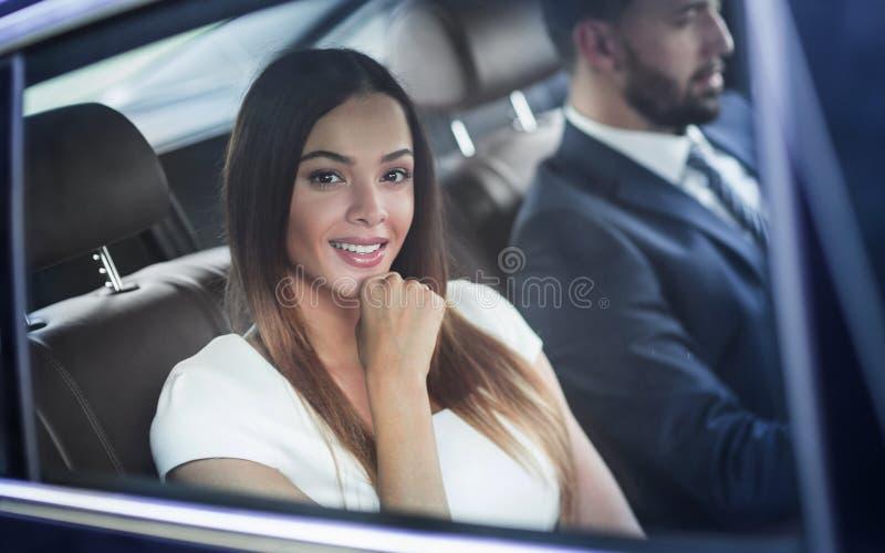 Portrait d'une femme dans une robe blanche dans sa voiture dans le siège arrière images libres de droits