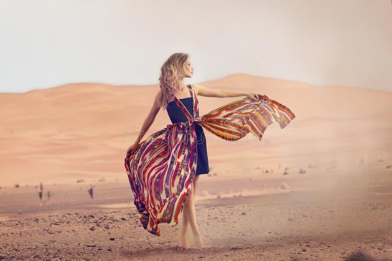 Portrait d'une femme de beauté dans une robe dans le désert chaud photos stock