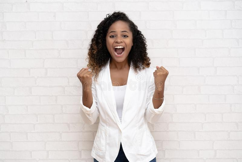 Portrait d'une femme de couleur afro-américaine de sourire dans des vêtements sport soulevant ses poings avec le visage avec plai photographie stock