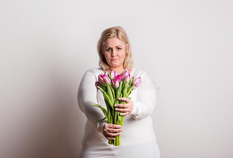 Portrait d'une femme de poids excessif attirante avec des tulipes dans le studio sur un fond blanc photos libres de droits