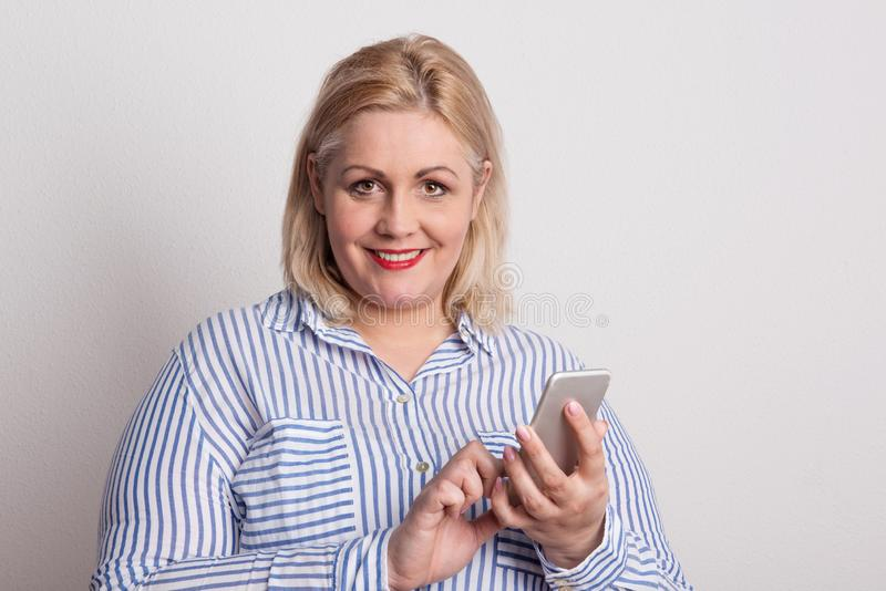 Portrait d'une femme de poids excessif attirante avec le smartphone dans un studio image libre de droits