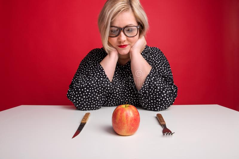 Portrait d'une femme de poids excessif attirante dans le studio, regardant une pomme sur la table photographie stock