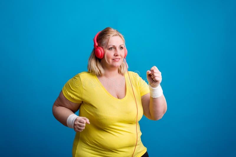 Portrait d'une femme de poids excessif attirante dans le studio sur un fond bleu, pulsant photo stock