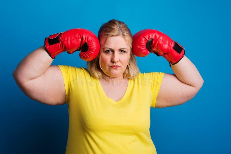 Portrait d'une femme de poids excessif avec les gants de boxe rouges dans le studio images stock