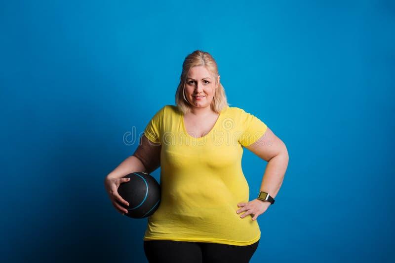 Portrait d'une femme de poids excessif heureuse avec le smartwatch et de boule lourde dans le studio photo libre de droits