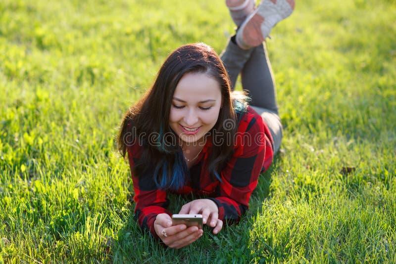 Portrait d'une femme de sourire se trouvant sur l'herbe verte et ? l'aide du smartphone dehors images stock