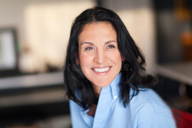 Portrait d'une femme espagnole mûre souriant à la caméra À la maison photo stock