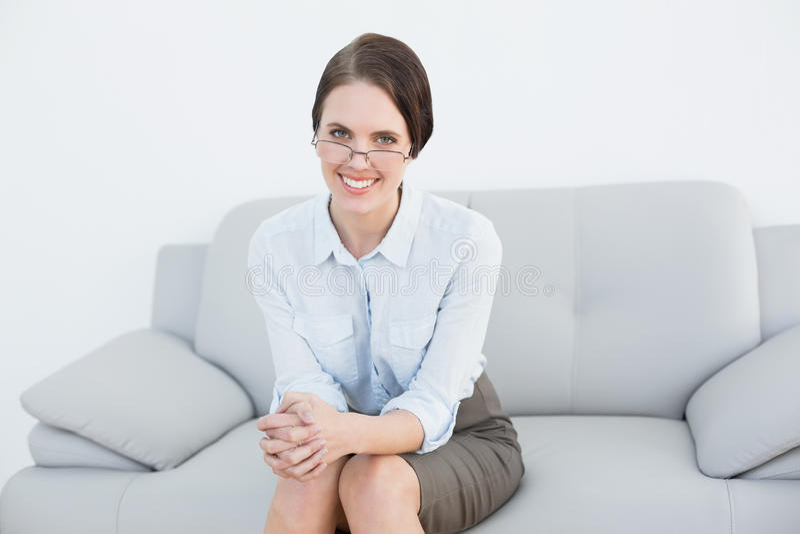 Portrait d'une femme futée de sourire s'asseyant sur le sofa photographie stock libre de droits