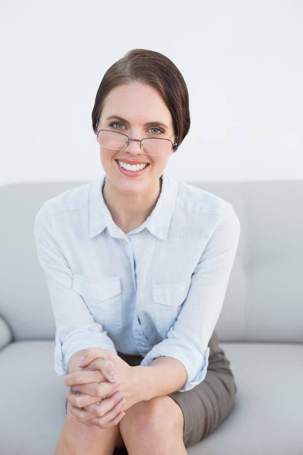 Portrait d'une femme futée de sourire s'asseyant sur le sofa image libre de droits